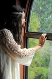 Looking out the window. A teenage girl looking through a window at nature Stock Photo