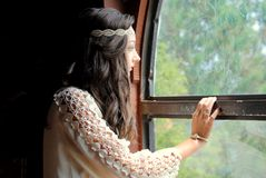 Looking out the window. A teenage girl looking through a window at nature Stock Images