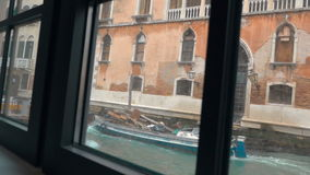 Looking out the window in Venice. VENICE, ITALY - FEBRUARY 20, 2015: Slow motion steadicam shot of woman opening curtian. Two cargo boats sailing on the canal stock footage