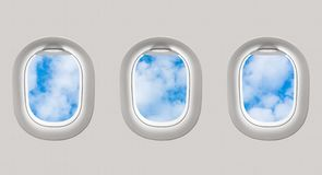 Looking out the windows of a plane to the blue sky and clouds Royalty Free Stock Photo