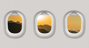 Looking out the windows of a plane to the mountains and sunset Royalty Free Stock Images