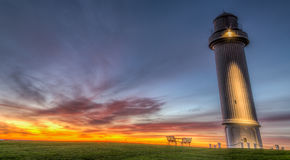 Looking out for you. A beautiful sunrise appears before a lighthouse Stock Photos