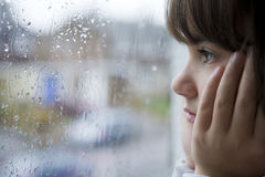 Looking out. Young child looking out of window on rainy day stock image