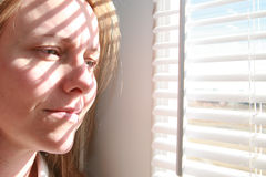 Looking Outside. A beautiful young woman looks out a window Royalty Free Stock Image