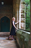 Looking Outside. Young blond woman standing on walkway beside rock wall looking out Royalty Free Stock Photography