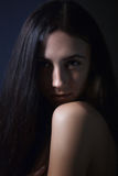 Looking over bared shoulder. Sensual girl in the dark looking at camera over bared shoulder Stock Photography