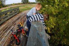 Looking Over A Bridge. After parking their bikes, a young girl and boy take a look at what lays under a bridge Stock Image