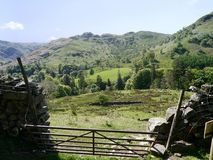 Looking over broken gate and fields to Arnison Crag, Lake District Royalty Free Stock Photos
