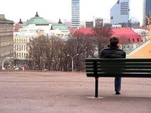 Looking over the city. Young man sitting on the bench and looking over the city of Tallin Stock Photos