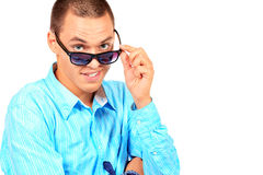 Looking over glasses. Portrait of a cool young man in sunglasses. Isolated over white background Royalty Free Stock Image