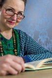 Looking over glasses. Middle aged woman reading a book looking over her glasses Royalty Free Stock Images