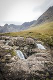 Looking over the rocks of the waterfalls towards the Cullins from the Fairy Pools on Skye royalty free stock images