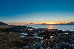 Portencross Jetty and Harbour Scotland on a Cold Sunset on Christmas Eve. Looking over the rocky harbour to the old jetty at Portencross in Seamill West Kilbride stock photos