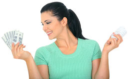 Looking Over Saving Energy Bill. Save energy concept. young woman holding bulb and money royalty free stock photos