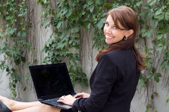 Looking over shoulder of business woman with laptop Royalty Free Stock Images