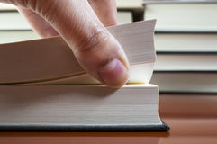 Looking for a page. Hand of a man looking for a page in a book royalty free stock photo
