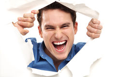 Looking through paper hole. Young man over white background Royalty Free Stock Photo