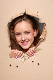 Looking through paper hole. Beautiful smiling woman looking through paper hole Stock Photo