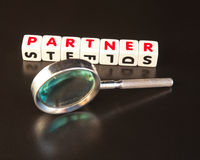 Looking for a partner. Text ' partner ' in red uppercase letters inscribed on white cubes next to a hand magnifier, dark surface Royalty Free Stock Photos