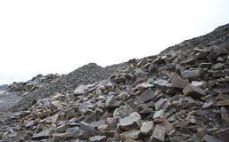 Looking past several piles of different rocks in a quarry Royalty Free Stock Images