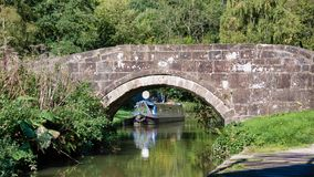 Peaceful canal scene. Looking at a peaceful canal scene with a boat moored and framed by an old stone bridge. The reflections are in the water royalty free stock photos