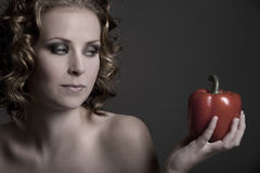 Looking at the pepper. Beautiful young blond woman looking at a pepper in her hand Royalty Free Stock Photography