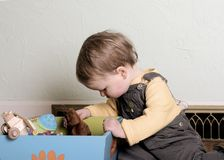 Looking for the perfect toy. Small child looks in toybox for toy -- vintage color stock photos