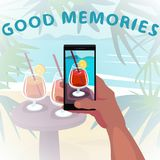 Looking at photo from vacation. Hand holds smartphone and show beach photo with cocktail from vacation. Remember about travel concept. First person view. Good Royalty Free Stock Images