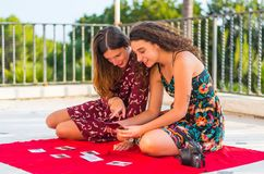 Looking at photos of friends. Two young white Caucasian girls sitting on a red blanket and looking at photographs of their friends stock photography