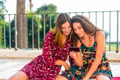 Looking at photos of friends. Two young white Caucasian girls sitting on a red blanket and looking at photographs of their friends royalty free stock photography