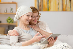Looking at photos. Woman with cancer and her friend looking at photos on tablet Stock Photography