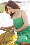 Looking into the picnic basket. A beautiful redhead looking in a picnic basket at the beach Royalty Free Stock Images