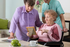 Looking at picture. Two aged women and young therapist looking at picture Royalty Free Stock Images