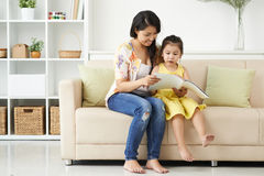 Looking at pictures. Mother and daughter looking at pictures in the magazine Royalty Free Stock Photos