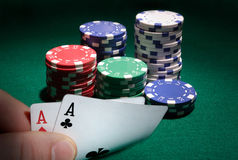 Looking at pocket aces during a poker game. Close up Stock Photos
