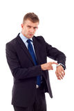 Looking and pointing at his watch. Businessman looking and pointing at his watch over white Royalty Free Stock Photo