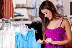 Looking at the price tag. Beautiful young woman looking at the price tag of a blouse while shopping in a store Stock Photography