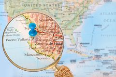 Looking in on Puerto Vallarta, Mexico. Blue tack on map of North America with magnifying glass looking in on Puerto Vallarta, Mexico royalty free stock image