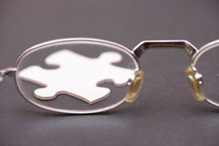 Looking at a puzzle. Glasses looking at a puzzle piece on a dark background for concepts like creativity, ideas or solutions - selective focus royalty free stock images