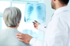 Looking at x-ray. Image of senior patient and doctor looking at x-ray in hospital Royalty Free Stock Photo