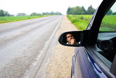 Looking in rear view mirror. Young handsome man is sitting in drivers place and looking in rear view mirror while is stopped in right side of the road. He is Stock Photos