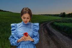 Looking at red poppy. Young woman in blue and white striped dress is holding a red poppy flower in her hands while standing on the country road near field of royalty free stock photos
