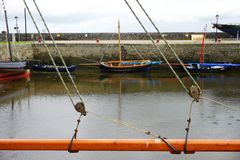 View through sailboat rigging of boats anchored against a stone seawall in a protected harbor in rural Ireland. Looking through the rigging at colorful boats Royalty Free Stock Photography