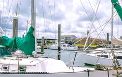Looking through sailboat yacht masts to new house construction b. Looking through sailboat yacht masts and rigging to new house construction building site in Royalty Free Stock Photos