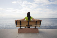 Looking at sea. Young woman sitting on a bench near the sea Royalty Free Stock Images