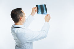 Turned back medical professional examining magnetic resonance image of leg. Looking serious. Waist up shot of a male practitioner lifting a mri picture of a royalty free stock photography