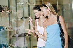 Looking through shop window. Young women looking through shop window Stock Photo