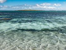 Distant view of the Holm of Papay seen from the shore of Papa Westray, Orkney. Looking from the shore of Papa Westray, the Holm of Papay, a small offshore island Royalty Free Stock Photo