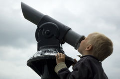 Looking Into The Sky. Boy looking into the sky through a telescope Royalty Free Stock Photography