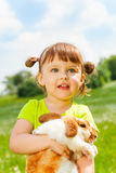 Looking small girl hugging rabbit in green field Royalty Free Stock Photography